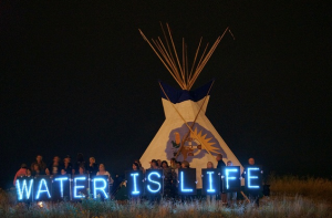 The Holders of the Light held several Idle No More water-related messages in front of the 2013 Indian Summer Festival's tipi, prominently located on the State Park Island in front of the Indian Summer grounds. (Photo: Light Brigading / Flickr)